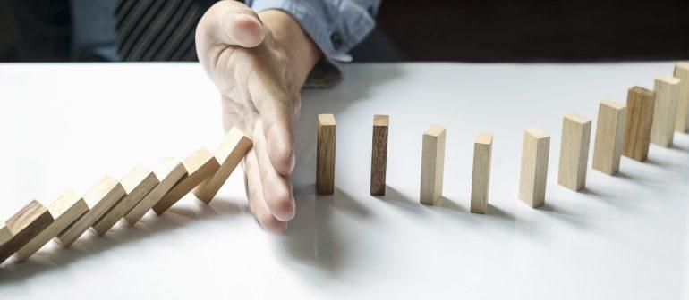 Hand-stoppt-Dominosteine